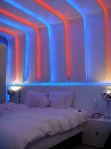 Pink and blue lighting above bed.